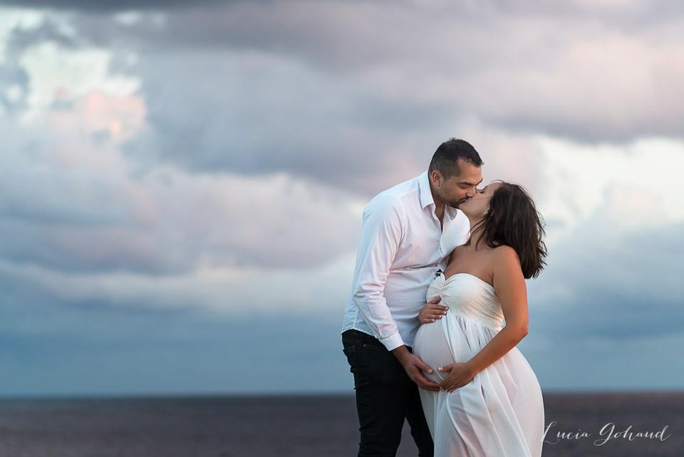 Couple pendant séance de maternité avec une ciel incroyable